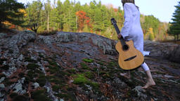 Woman with guitar relaxing in mountains Live Action