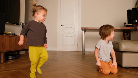 Cheerful small boy playing with sister at home Live Action