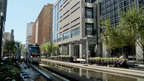 A rapid transit train moves quickly through downtown Houston with fountains dancing Footage