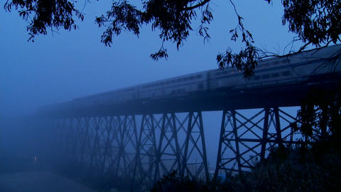 An Amtrak passenger trains speeds across a bridge in the fog at night Footage
