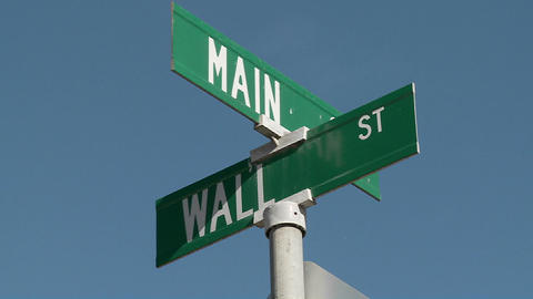 A street sign indicates the intersection of Main and Wall Streets Footage