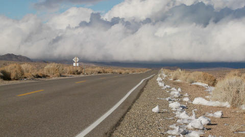 Clouds form over a remote desert road Stock Video Footage