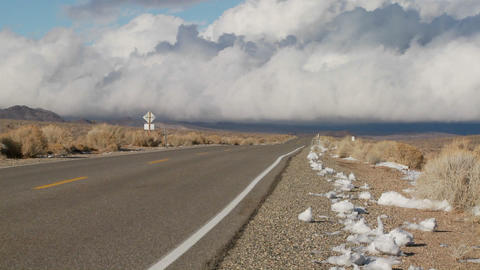 Clouds form over a remote desert road Footage