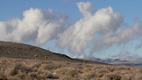 Time lapse of clouds moving behind a ridge in the desert Stock Video Footage