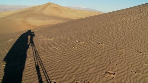The shadow of a filmmaker with a tripod in shadow filming in Death Valley against the vast arid dune Footage