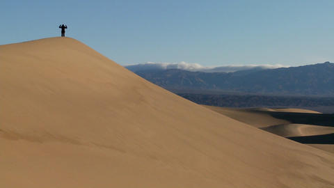 A person jumps up and down on a desert dune to symbolize... Stock Video Footage