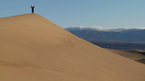A person jumps up and down on a desert dune to symbolize victory or achievement of a goal Footage