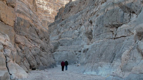 A Senior Man And Woman Hike In A Canyon In Death Valley stock footage