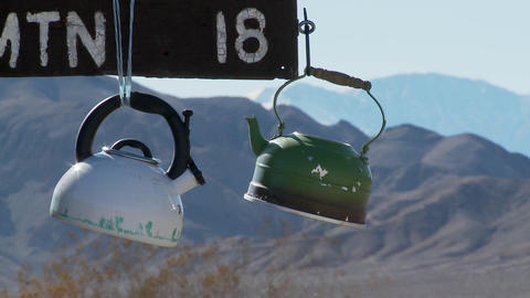 Tea pots hang from a sign in Death Valley National park Stock Video Footage