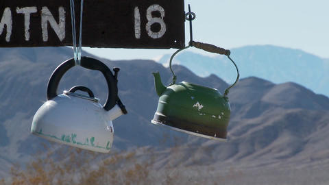 Tea pots hang from a sign in Death Valley National park Footage