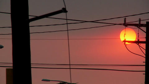 A orange ball of sun sets behind power lines during fire season in California Footage