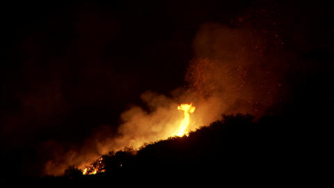Firefighters battle a raging California wildfire at night... Stock Video Footage