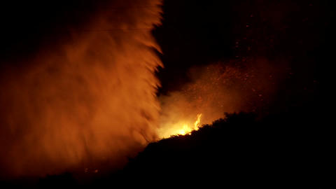 Firefighters battle a raging California wildfire at night by performing a water drop from an aerial Footage