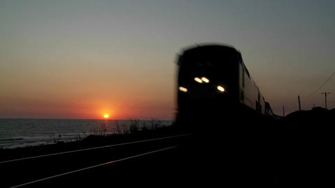 Beautiful shot of an Amtrak train passing by a California beach at sunset Footage