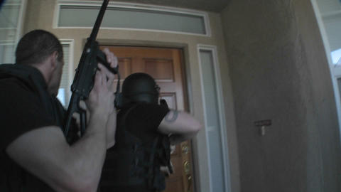 DEA officers with arms drawn perform a drug raid on a house Stock Video Footage
