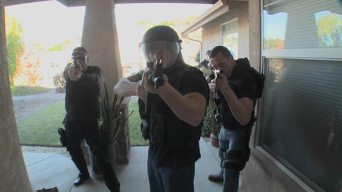 DEA or SWAT officers with arms drawn perform a drug raid... Stock Video Footage