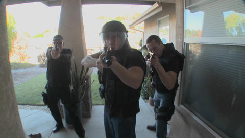 DEA or SWAT officers with arms drawn perform a drug raid on a house Footage