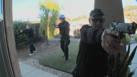 DEA Or SWAT Officers With Arms Drawn Pound On The Door Before Performing A Drug Raid On A House stock footage