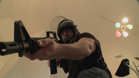 A SWAT team with DEA officers clears a house during a drug raid and holds a suspect at gunpoint Footage