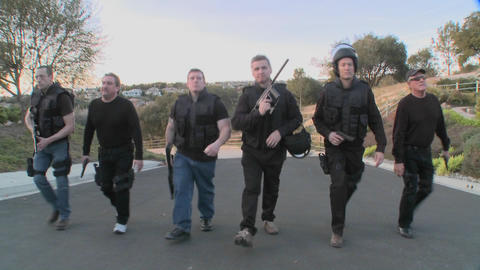 A SWAT team of DEA agents walks in a macho way up a street in a display of force Footage