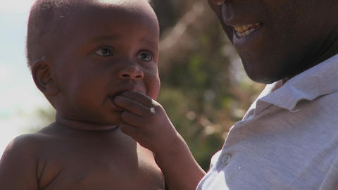A man holds a small baby in Africa Stock Video Footage