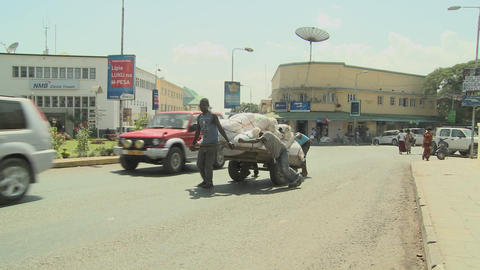 Men work hard to push a cart up a street in Arusha, Tanzania Footage