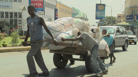 Men work hard to push a cart up a street in Arusha, Tanzania Stock Video Footage