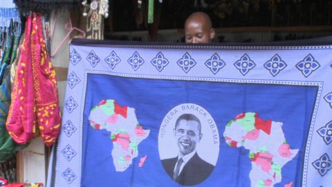 A vendor holds up a blanket with Barack Obama picture on... Stock Video Footage