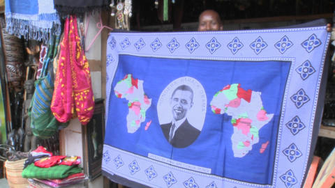 A vendor holds up a blanket with Barack Obama picture on it in kenya Footage