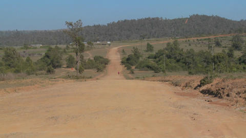 A man walks on a lonely dusty dirt road in Africa Stock Video Footage