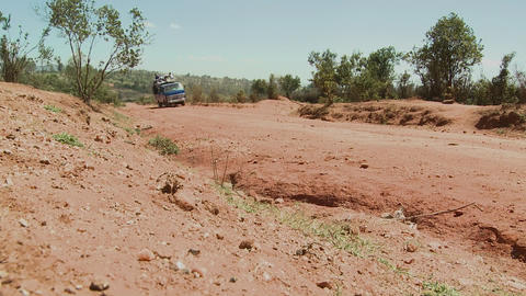 A van crowded with travelers makes its way along a dirt road in Africa Footage