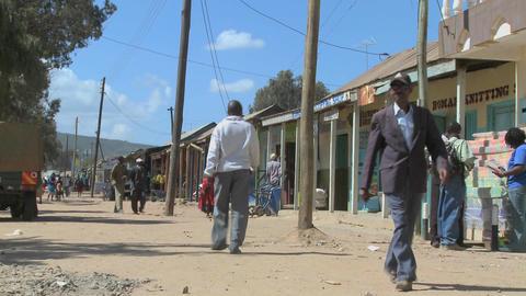 Pedestrians walk on the dirt streets of Maralal in Northern Kenya Footage