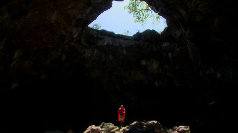 Spectacular tilt down shot of a Masai warrior stading in a huge pool of light in a cave in Kenya Footage