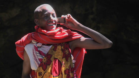 A Masai man in tribal costume talks on a cell phone Stock Video Footage