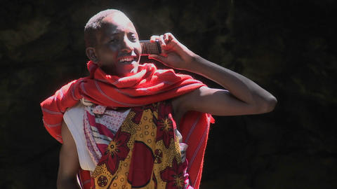 A Masai man in tribal costume talks on a cell phone Footage