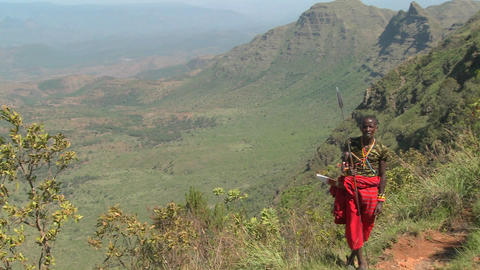 A Masai warrior stands at the edge of a vast canyon in... Stock Video Footage
