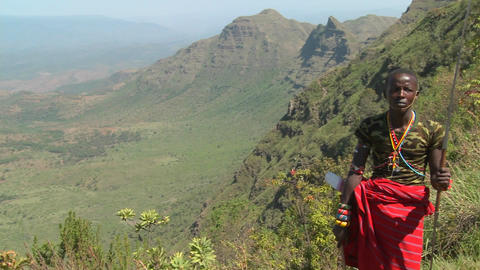Pan across to a Masai warrior standing at the edge of a... Stock Video Footage