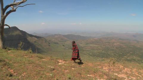 A masai warrior walking along a vast landscape in Northern Kenya Footage