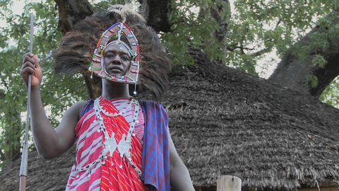 Pan to a Masai warrior in full headdress Stock Video Footage