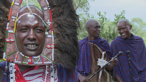 Masai warrior in full headdress with two friends nearby Stock Video Footage