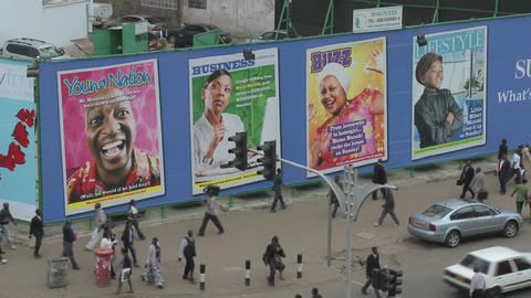 Handprinted billboard signs along a busy street in kenya Stock Video Footage
