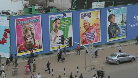 Handprinted billboard signs along a busy street in kenya Stock Video Footage