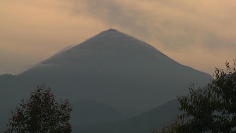 A beautiful time lapse of clouds blowing over the top of a Virunga volcano on the Rwanda Congo borde Footage