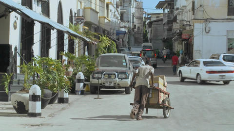 A man pushes a handcart up a narrow boulevard in Stone Town, Zanzibar Footage