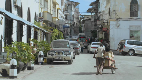 A man pushes a handcart up a narrow boulevard in Stone... Stock Video Footage