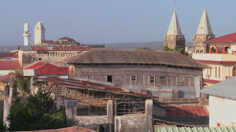 A rooftop overview establishing shot of Stone Town, Zanzibar with mosques and church steeples Footage