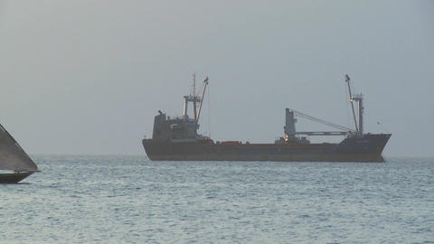 A dhow sailboat sails bast a modern freighter cargo ship... Stock Video Footage