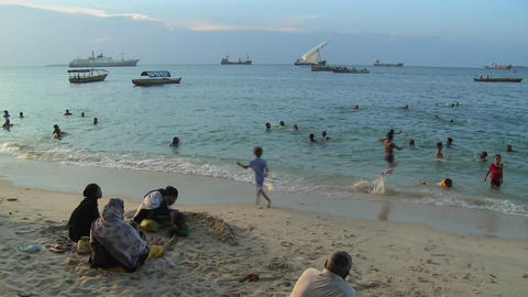 Children play and swim on the beach in Stone Town, Zanzibar at sunset while sailboats sail in the di Footage