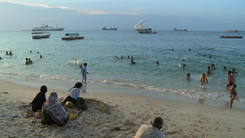 Children play and swim on the beach in Stone Town,... Stock Video Footage