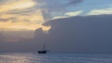 A distant boat sails along the shores of Zanzibar at sunrise Stock Video Footage